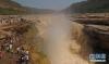 7月12日,游人在观赏黄河壶口瀑布。黄河壶口瀑布位于山西吉县和陕西宜川之间。