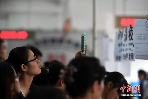 资料图:在人海里用手机拍摄招聘资料的应聘者。中新社记者 李进红 摄