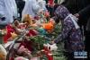 3月27日,在俄罗斯首都莫斯科,一名儿童摆放鲜花悼念克麦罗沃火灾遇难者。新华社发(叶甫盖尼·西尼岑摄)