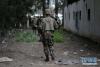 4月11日,在阿尔及利亚卜利达省,士兵们在军机坠毁现场附近搜寻坠毁飞机零件,以便调查事故原因。