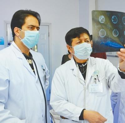2018年3月,比拉尔·海帝(左)与同事探讨病人病情。   神木市医院供图