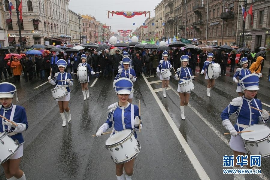 """5月1日,在俄罗斯圣彼得堡的涅瓦大街,人们冒雨参加""""五一""""游行,庆祝""""五一""""国际劳动节。 新华社发(莫京娜摄)"""