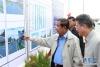 5月7日,在柬埔寨金边,柬埔寨首相洪森(前左)和公共工程与运输大臣孙占托(前右)在开工仪式现场看项目介绍和效果图。