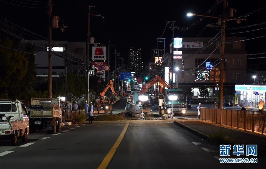 6月18日,在日本大阪,工程人员抢修破损道路。
