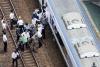 6月18日,在日本大阪,乘客在火车暂停运行后走上铁道。新华社/美联