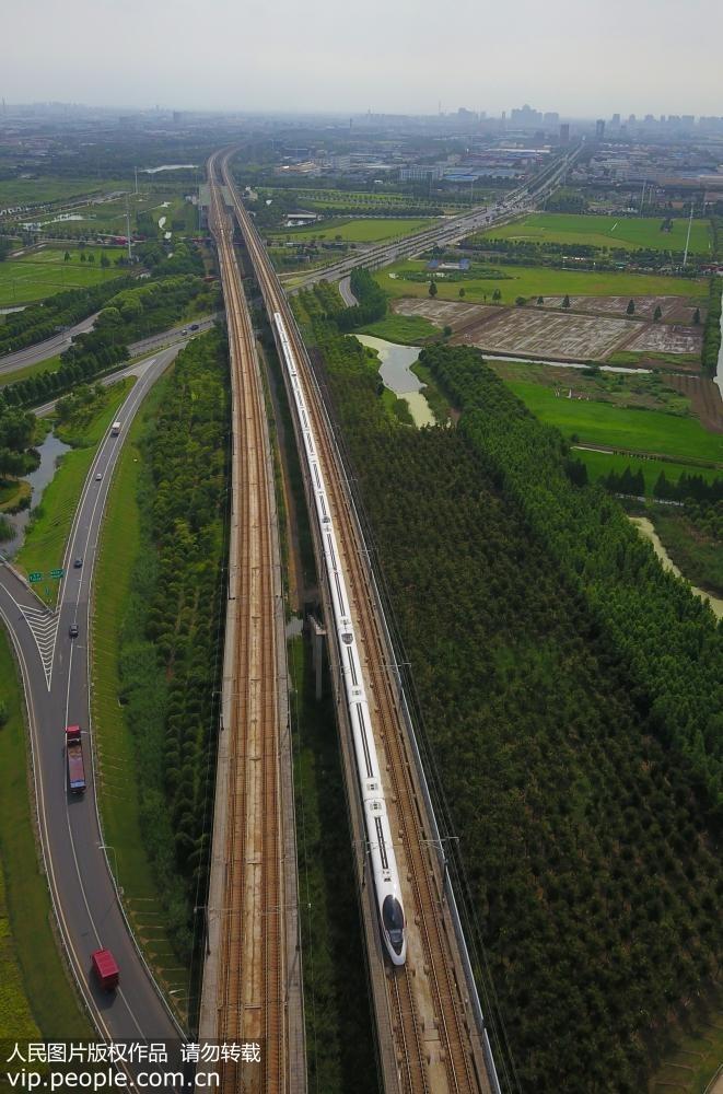 """7月2日,无人机航拍疾驶在京沪高铁江苏苏州段的加长版""""复兴号""""列车。"""