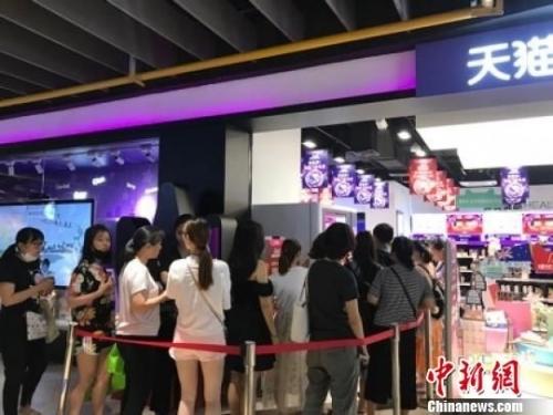 图为杭州西湖银泰天猫国际线下店,消费者排着长队。供图