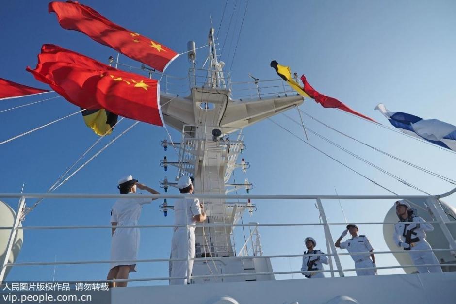 信号部门官兵升起国旗和军旗。
