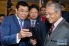 4月18日,在马来西亚普特拉贾亚,马来西亚总理马哈蒂尔(右)在5G技术展上听取华为5G智能手机的介绍。 由马来西亚通信与多媒体部主办的马来西亚5G技术展18日在该国行政首都普特拉贾亚开幕,会上展出了5G通信和应用技术,华为等中国企业参展。 新华社记者 朱炜 摄